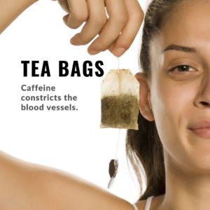 Brown haired woman eyes showing teabag as eye care on clean white background