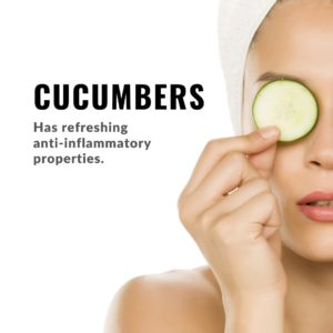 Woman after shower photo with white towel on hair on white background using a slice of cucumber as eyecare.