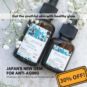 Japanese skincare products lying on a marble table with white small flowers decor