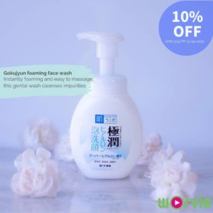 Japanese skincare face wash standing on a gray marble surface decorated with baby pink flowers