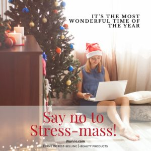 Woman on a blue dress wearing Santa hat sitting on the floor with Christmas tree and decors, online Christmas shopping using a white laptop and credit card