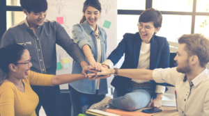 Marketing people in different race showing hands for support in their office