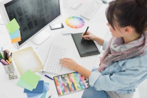 Young Japanese woman doing a graphic design task on a computer table with designing tools around her